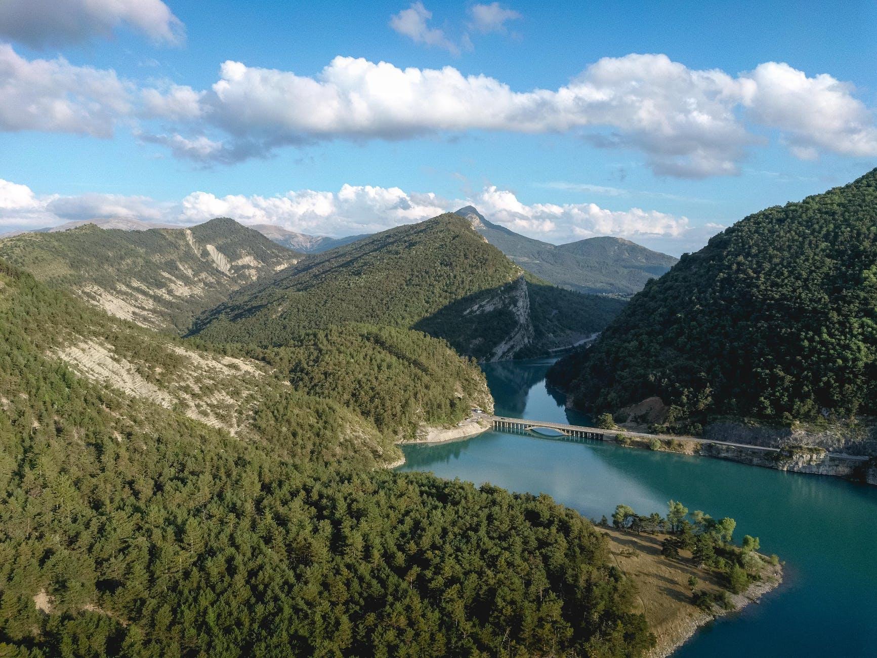 green mountains near lake under blue sky